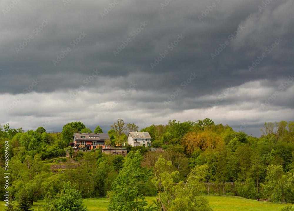 Fototapeta Ciemne, zachmurzone niebo. Cisza przed burza. Male domki na wzgorzu.  Wiosenna aura.  Dom w lesie.