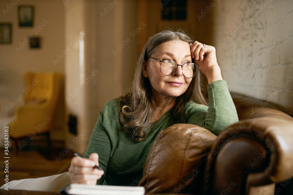 Fototapeta Stylish inspired middle aged woman writer wearing glasses sitting in leather couch with pen making notes. Attractive mature female artist sketching or teacher preparing tasks for online lessons