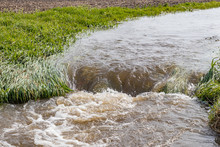 Water Flowing In Farm Field Waterway After Heavy Rain And Storms Caused Flooding. Concept Of Soil Erosion, Water Runoff Control And Management