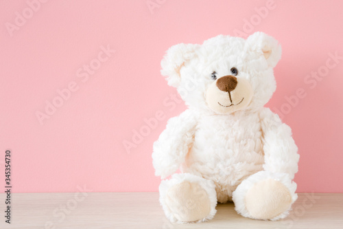 Cuadros en Lienzo Smiling white teddy bear sitting on table at pastel pink wall background