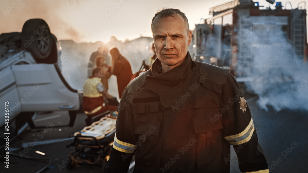 Fototapeta Portrait of the Brave Firefighter Walking to the Camera. In Background Courageous Heroes Paramedics and Firemen Rescue Team Fight Fire, Smoke and Save People's Lives