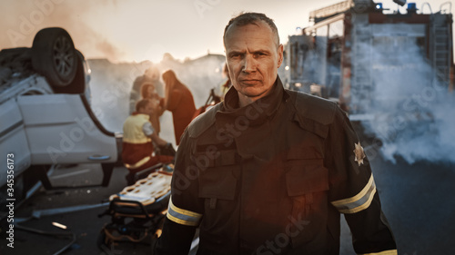 Fototapeta Portrait of the Brave Firefighter Walking to the Camera. In Background Courageous Heroes Paramedics and Firemen Rescue Team Fight Fire, Smoke and Save People's Lives obraz