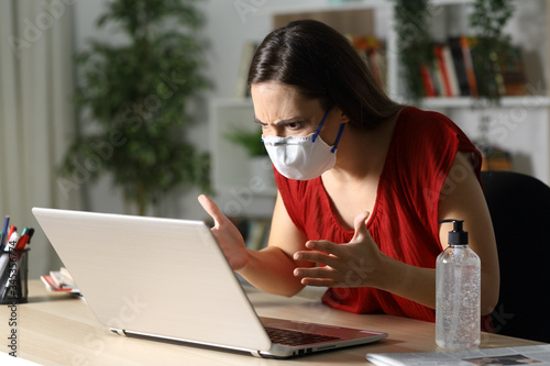 Angry girl checking laptop on coronavirus confinement Canvas Print