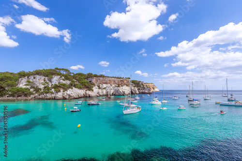 View of the most beautiful bay Cala Macarella of the island Menorca with emerald water and a lot of yachts on the sea. Balearic islands, Spain