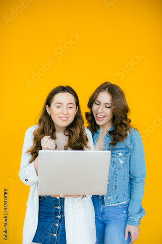 Image of delighted multinational girls rejoicing and holding laptop computer iso Wallpaper Mural