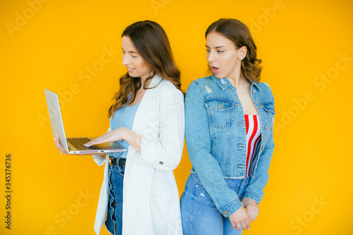 Image of delighted multinational girls rejoicing and holding laptop computer iso Canvas Print