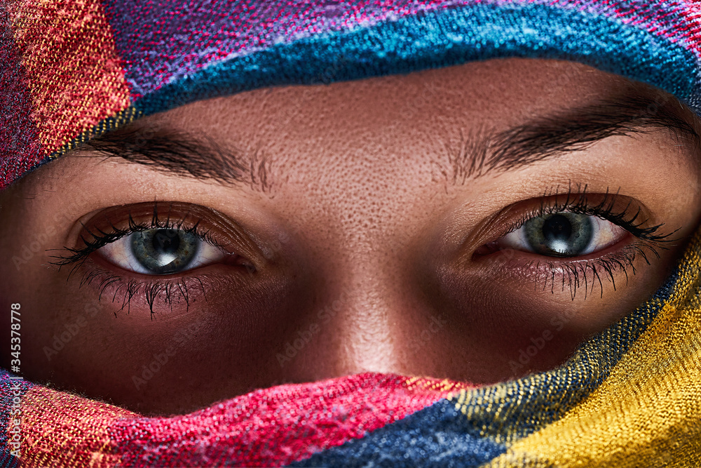 Fototapeta Eastern woman in a colored head scarf with narrowed eyes close up