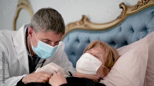 Photo Doctor using stethoscope for auscultate caucasian elderly female patient with face mask at home