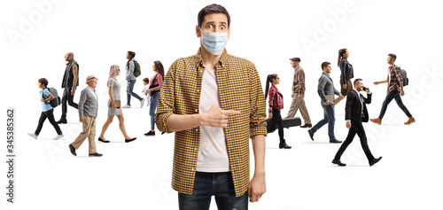Disappointed man with a protective face mask pointing at a group of people walki Fototapet