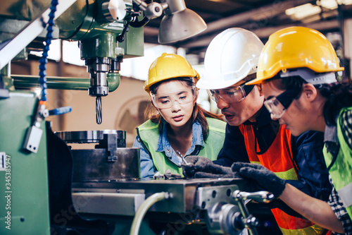 Fotografia Asian male technician manager showing case study of factory machine to two engineer trainee young woman in protective uniform