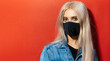 canvas print picture - Studio portrait of young blonde girl with blue eyes wearing respiratory face mask against coronavirus. Background of red color with copy space.
