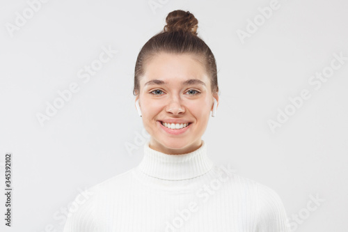 Headshot of young woman wearing white turtleneck sweater and wireless earphones, Tablou Canvas