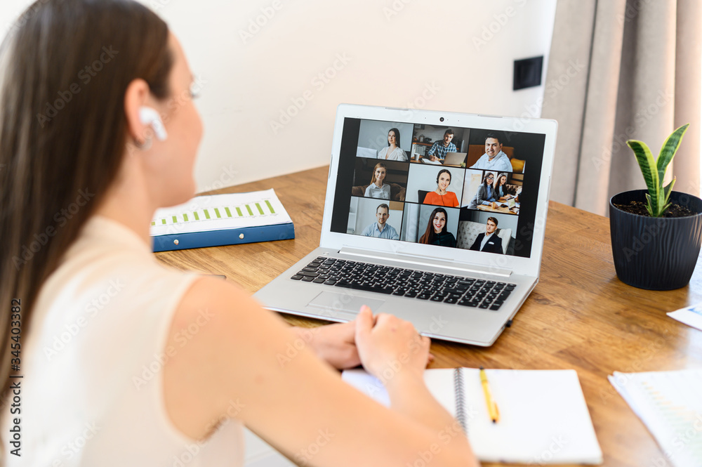 Fototapeta Virtual video conference, online meeting with a many employees together. A young woman is communicating via video call with coworkers, a several webcam shot of people on the laptop screen