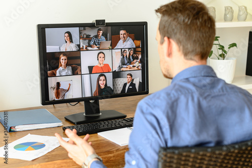 Obraz Virtual conference with employees. A young man in formal shirt using pc for video call, he has video meeting with several people together. Remote work concept - fototapety do salonu