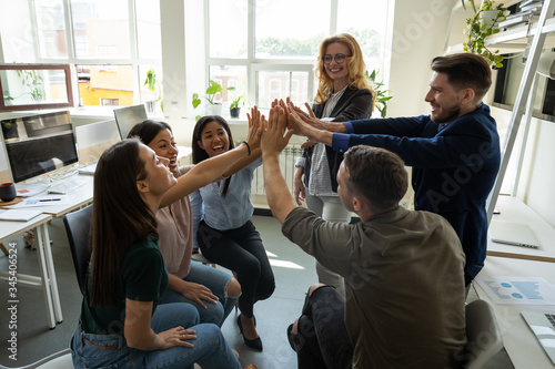 Fototapeta Multiracial employees team with male leader, coach giving high five at company meeting, female teacher with interns celebrating achievement, corporate success of teamwork, team building activity. obraz na płótnie