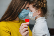 Young Mommy Hugs Cute Preschool Daughter In Protective Medical Masks Sitting On Bed, Holding Red Heart A Way To Show Appreciation And To Thank All Essential Employees During Covid-19 Pandemics