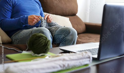 Cuadros en Lienzo Young man watching lesson online and knitting from home
