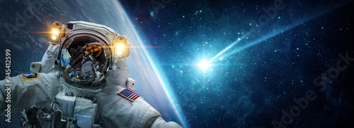 Leinwand Poster Astronaut in orbit of planet Earth against the background of a falling meteorite, asteroid, comet
