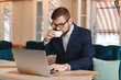 Young businessman drinking coffee during work in cafe