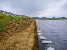 Working Edge Of A Landfill Expansion Project With Active Landfill, Clay Cover, And HDPE Synthetic Liner In The Same Picture