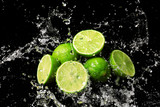 Fresh limes with water splashes on dark background
