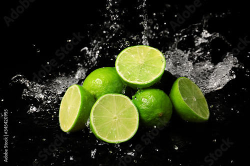 Fresh limes with water splashes on dark background Wallpaper Mural
