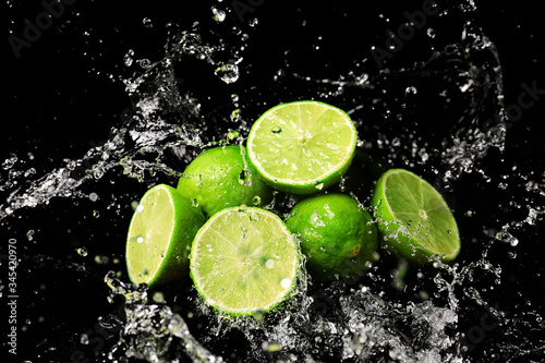 Fototapeta Fresh limes with water splashes on dark background obraz