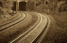 Railroad, Two Tracks. The Frame Is A Smooth Rotation. Entry Into The Tunnel. Black And White Photo, High Contrast. The Picture Shows Trees, Bushes, Grass. Sepia.