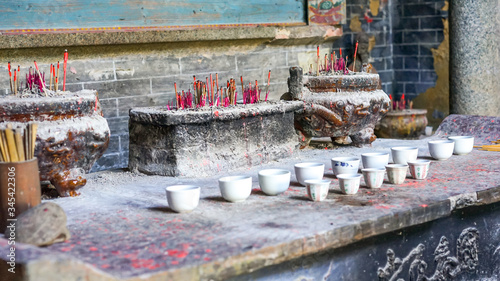 An old traditional Buddhist temple in China with aroma sticks, little cups and o Фотошпалери