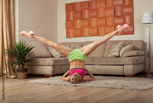 Valokuvatapetti young blonde sporty fit woman doing gymnastic and yoga exercis at home training