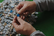 Closeup Of Mature Hands Holding Jigsaw Puzzle Piece