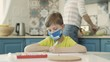 Boy In Medical Mask Sits At Table In The Kitchen And Draws.