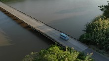 Aerial Tracking Shot Of A Blue Minibus Taxi Crossing A Small Bridge Over The Umzimkulu River In South Africa Before Continuing Along A Long Stretch Of Highway. Concept: Road Trip