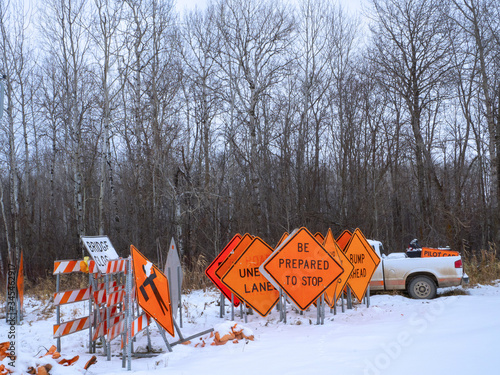 Photo Orange Road Warning Signs stand in winter snow, near a Pilot Car pickup, as they await summer construction season in Minnesota
