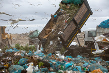 Rubbish Piled On A Landfill Full Of Trash With Vehicles Working