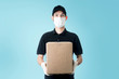 canvas print picture - Delivery man with uniform mask and glove holding box. Cyan background.