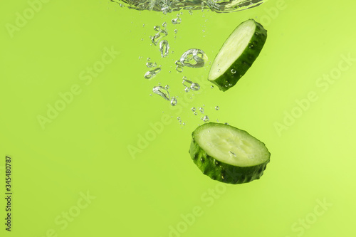 Fototapeta Falling of fresh cucumber slices into water against color background obraz