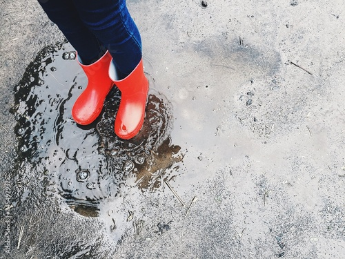 Low Section Of Child Standing On Puddle Fototapeta