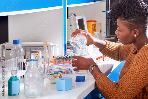 Photo Young African female tech or scientist is pouring buffer solution from bottle to bottle for blood test analysis assay in modern research laboratory