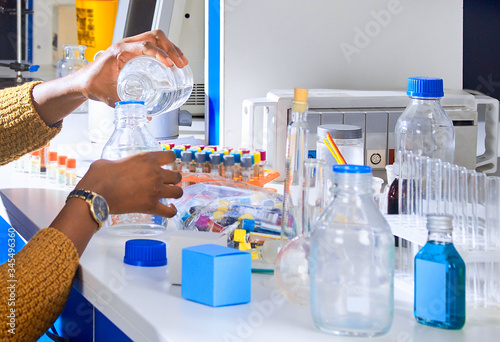 Young African female tech or scientist is pouring buffer solution from bottle to bottle for blood test analysis assay in modern research laboratory Canvas Print