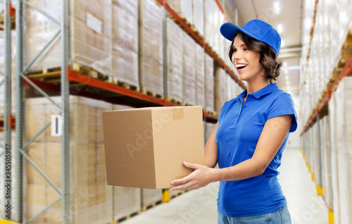 Fototapeta logistics, mail service and shipment concept - happy smiling delivery girl with