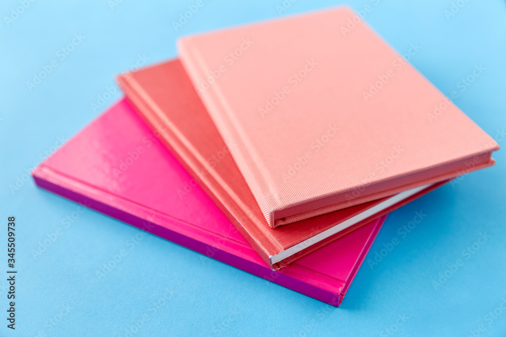 Fototapeta education and object concept - notebooks or books on blue background