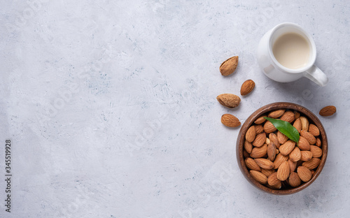 Photo nuts almonds in a wooden bowl with almond milk in a milk jug and raw nuts  on a