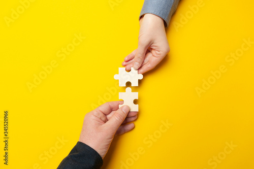 Two hands connect puzzles on a yellow background. Cooperation and teamwork in business. Collaboration people for success.