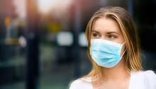 Epidemic Corona Virus Masked Girl On The Blur Background Of The City. Coronavirus Flu Travel Concept Wide Banner Panorama. Woman In Face Mask Copy Space For Text