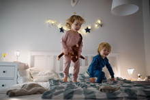 Two Small Children Jumping On Bed Indoors At Home, Having Fun.