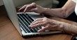 Close up of elderly woman hands typing on notebook. Old woman's hand writing on laptop at home. Hand-held shot, single shot, close-up, 4K.