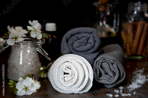 Beauty spa treatment and relax concept. Towel, sea salt and essential oils on a dark background