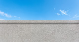 Concrete clean wall as border and blue sky with white clouds as background