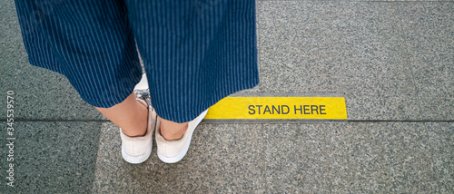 Cuadros en Lienzo Banner photo of Asian woman standing on social distancing sign for keep distance and queue for entrance subway train a new normal life trend